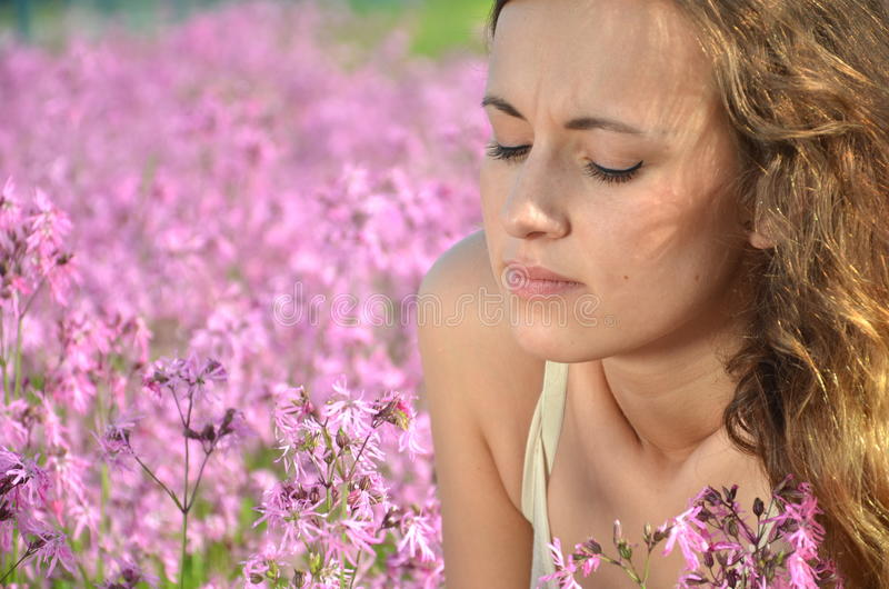 Chica joven atractiva hermosa en prado magnífico por completo de flores salvajes foto de archivo