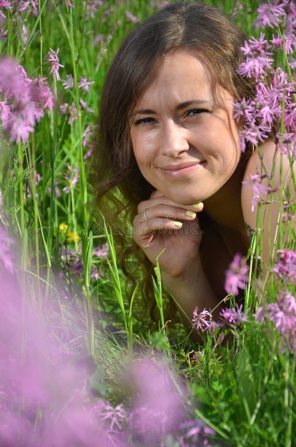Chica joven atractiva hermosa en prado magnífico por completo de flores salvajes imagen de archivo libre de regalías
