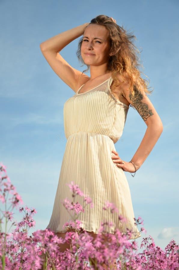 Chica joven atractiva hermosa que se coloca en prado magnífico por completo de flores salvajes imagen de archivo libre de regalías