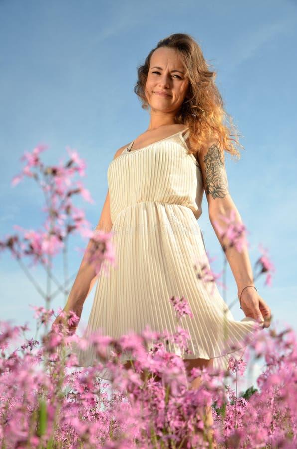 Chica joven atractiva hermosa que se coloca en prado magnífico por completo de flores salvajes fotografía de archivo
