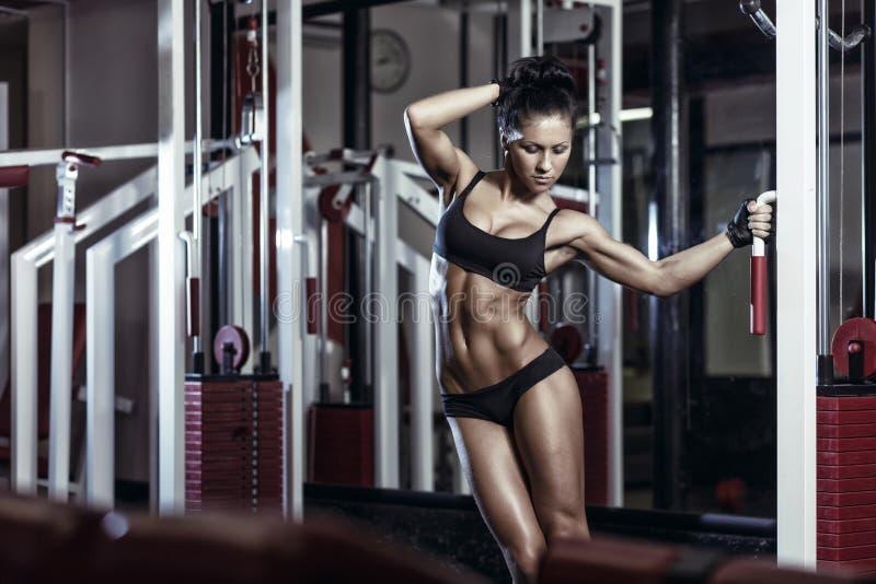 Chica joven atractiva que presenta en el gimnasio y que sostiene la máquina encendido de entrenamiento imagen de archivo