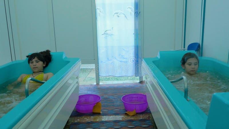 Chica joven atractiva que se baña en un baño en un balneario de la salud Las chicas jóvenes disfrutan de los baños terapéuticos a fotografía de archivo