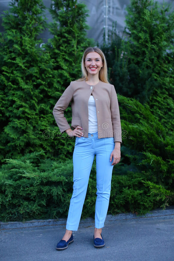 Chica joven atractiva que sonríe y que presenta a la cámara y a los soportes adentro fotografía de archivo