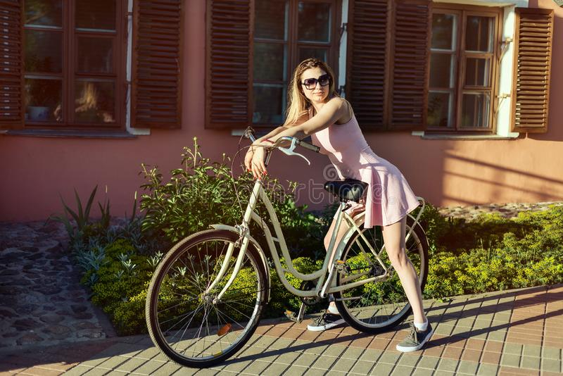 Chica joven atractiva sobre los vidrios que llevan y un vestido rosado po de una bicicleta fotos de archivo