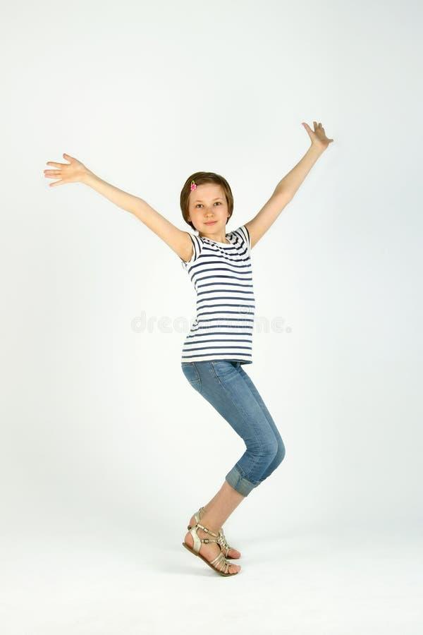 Chica joven bonita alegre que salta y que levanta las manos foto de archivo libre de regalías