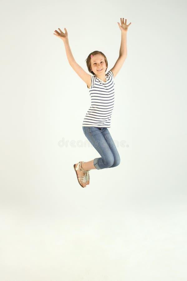 Chica joven bonita alegre que salta y que levanta las manos fotos de archivo
