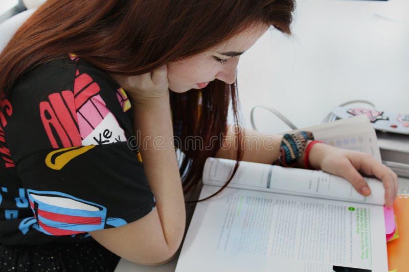Chica joven bonita con estudio hermoso largo del pelo en la universidad a foto de archivo