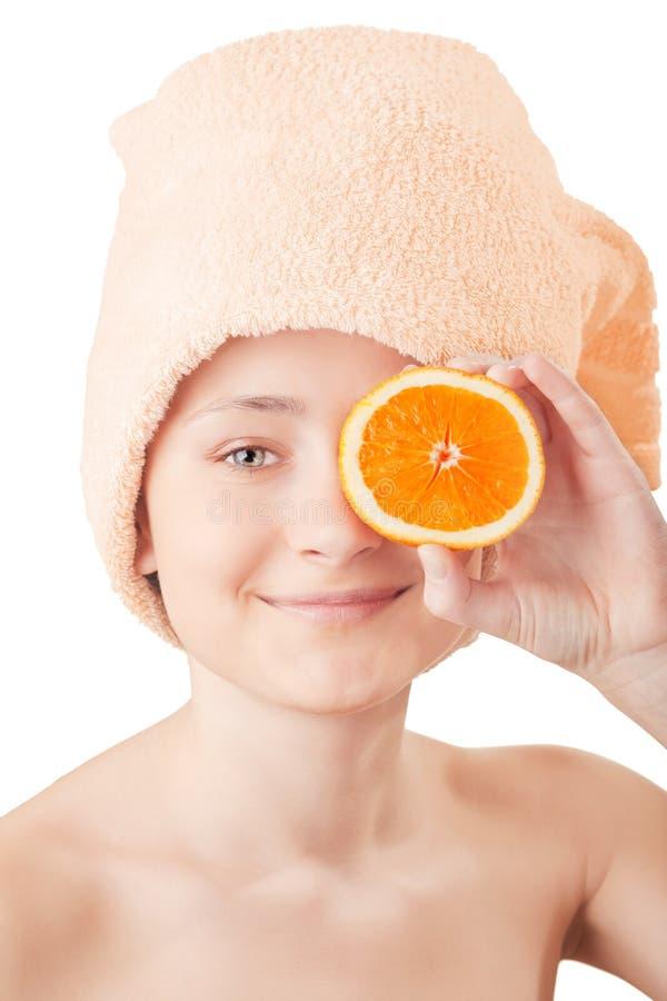 Chica joven bonita con una naranja