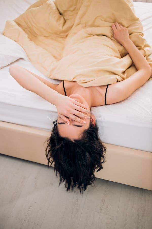 Chica joven bonita del retrato en cama en el apartamento moderno por la mañana imágenes de archivo libres de regalías