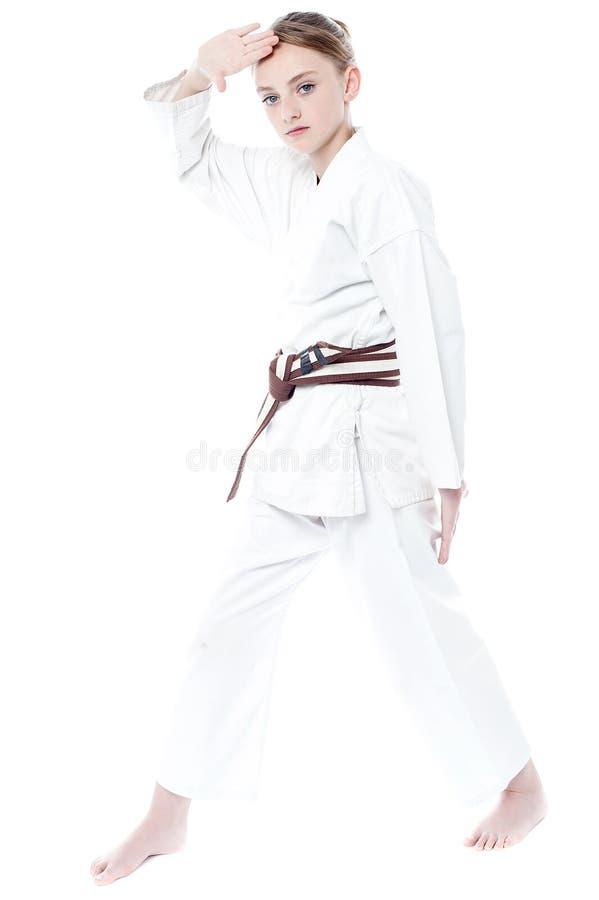 Chica joven bonita en uniforme del karate fotos de archivo