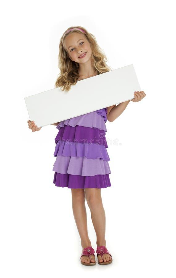 Chica joven bonita que lleva a cabo la muestra en blanco fotografía de archivo