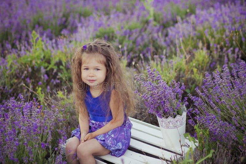 Chica joven bonita que se sienta en campo de la lavanda en navegante agradable del sombrero con la flor púrpura en ella fotografía de archivo libre de regalías