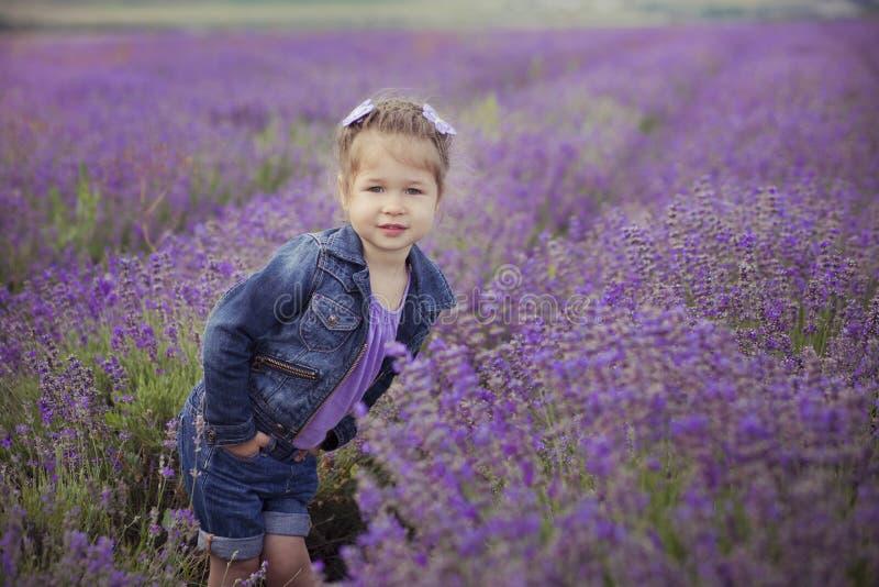 Chica joven bonita que se sienta en campo de la lavanda en navegante agradable del sombrero con la flor púrpura en ella imagenes de archivo