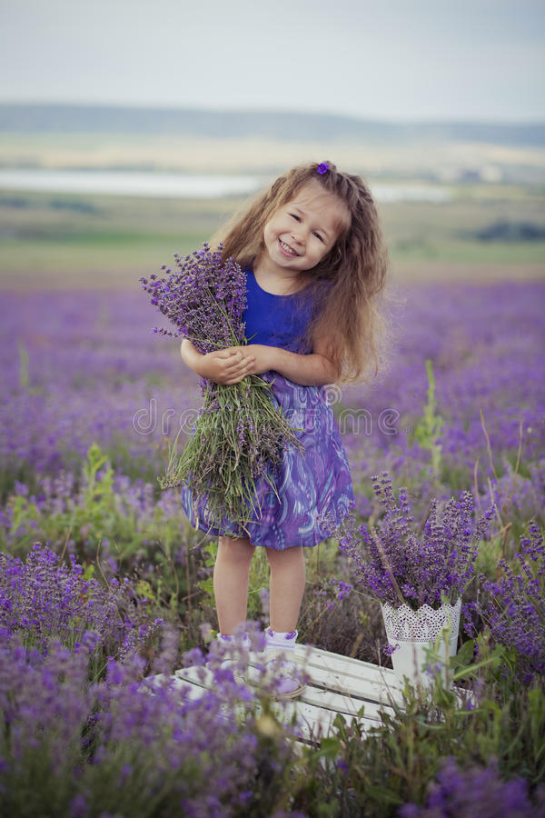 Chica joven bonita que se sienta en campo de la lavanda en navegante agradable del sombrero con la flor púrpura en ella fotos de archivo libres de regalías