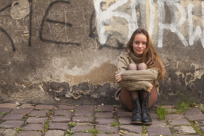 Chica joven bonita que se sienta en el pavimento cerca de una pared de piedra de una casa Caminata en la ciudad imagenes de archivo