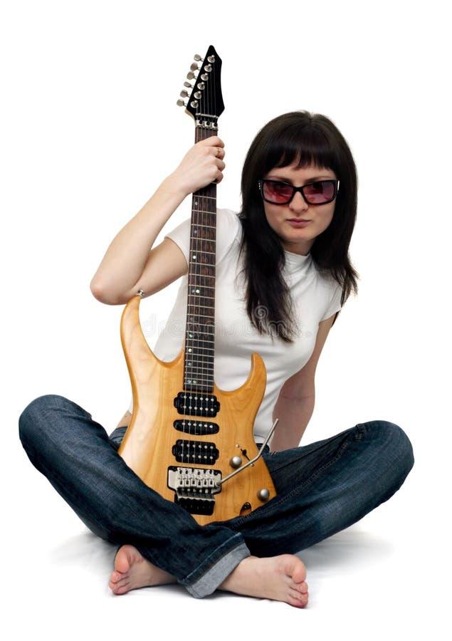 Chica joven bonita que sostiene una guitarra eléctrica fotografía de archivo libre de regalías