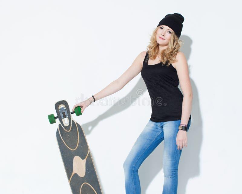Chica joven brillante de moda hermosa en vaqueros, una camiseta negra y el sombrero que presentan con un longboard fresco en las  foto de archivo libre de regalías