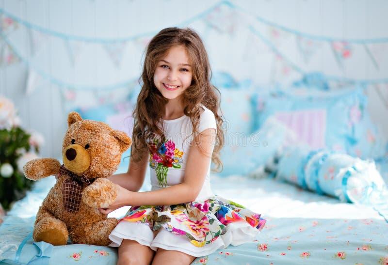 Chica joven cabelluda rizada muy linda que se sienta en la cama con t suave imagen de archivo