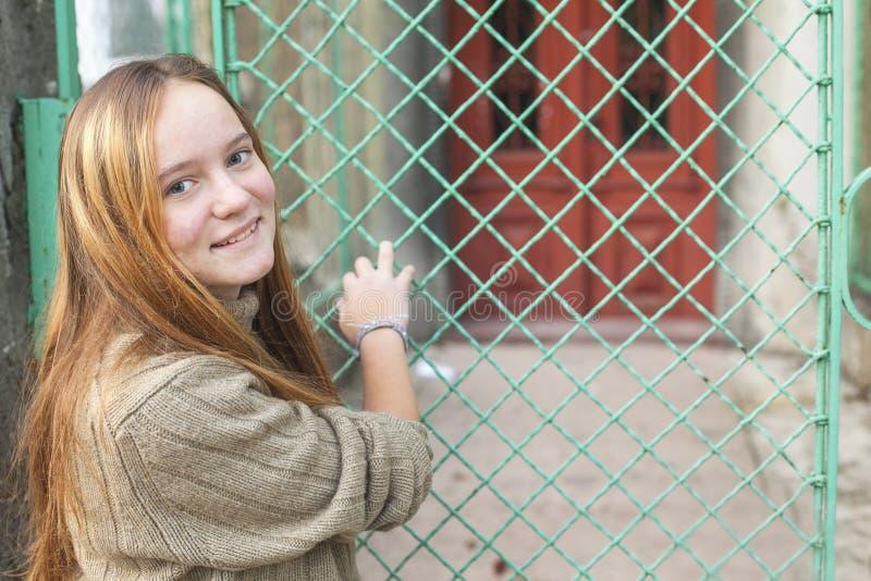 Chica joven cerca de la cerca en la calle de la ciudad foto de archivo libre de regalías
