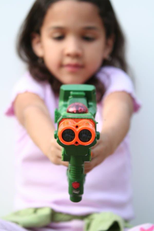 Chica joven con el arma del juguete fotos de archivo