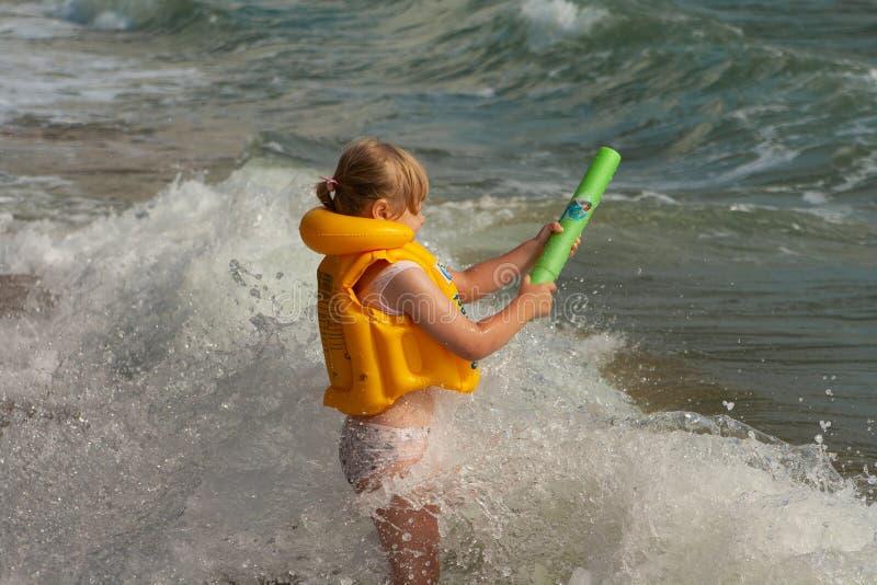 Chica joven con el chaleco salvavidas amarillo En la orilla con las ondas Pistola de agua foto de archivo libre de regalías