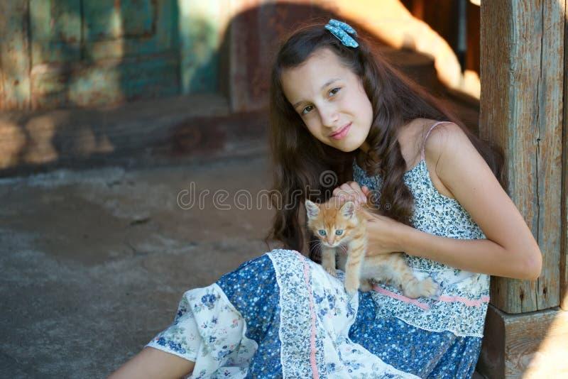 Chica joven con el gatito rojo foto de archivo