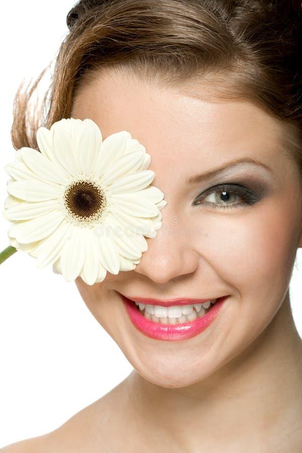 Chica joven con el gerber blanco delante de su cabeza foto de archivo libre de regalías