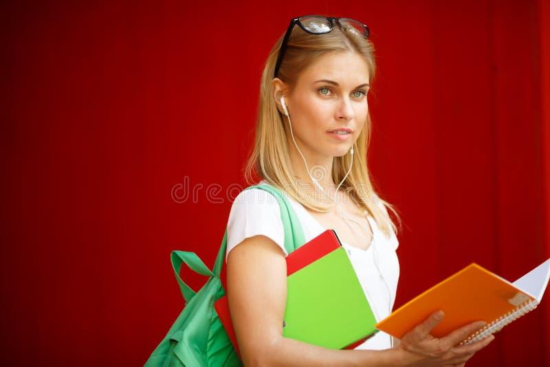 Chica joven con el libro en auriculares en el fondo vacío de Brown imagen de archivo libre de regalías
