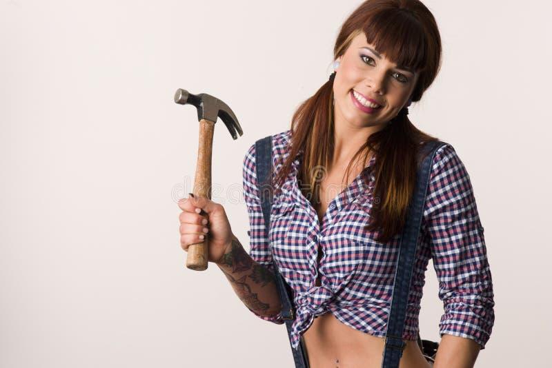 Chica joven con el martillo foto de archivo