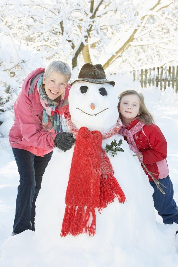 Chica joven con el muñeco de nieve del edificio de la abuela imagen de archivo