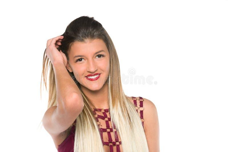 Chica joven con el pelo largo que presenta en estudio foto de archivo