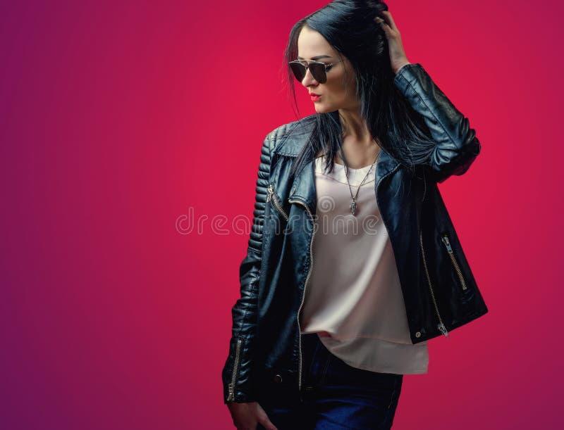 Chica joven con el pelo negro en una chaqueta de cuero y un sungl elegante fotos de archivo