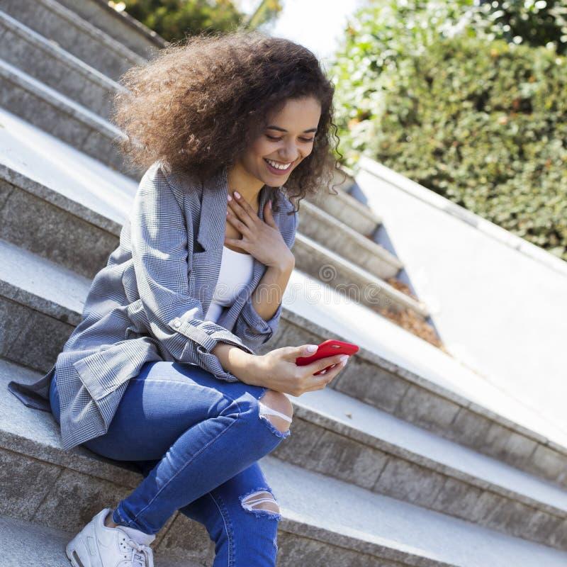 Chica joven con el pelo rizado oscuro usando el tel?fono en un parque de la ciudad imagen de archivo