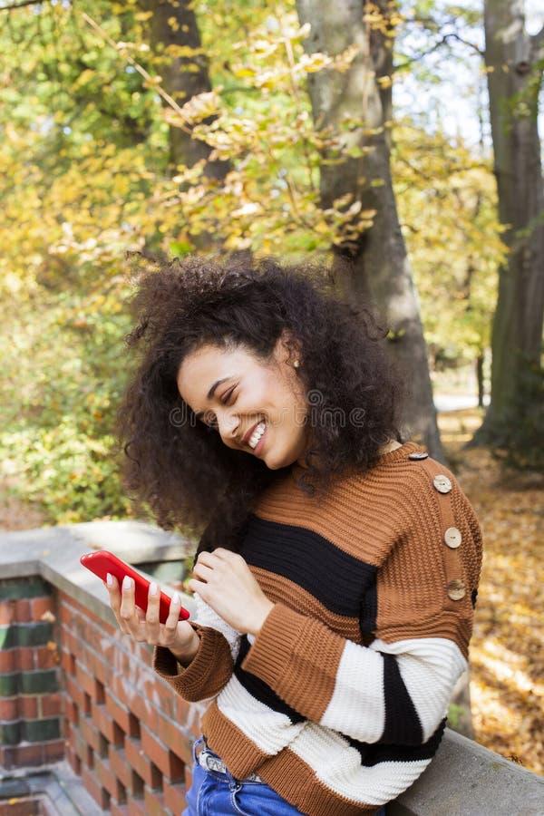 Chica joven con el pelo rizado oscuro usando el tel?fono en un parque de la ciudad imagenes de archivo