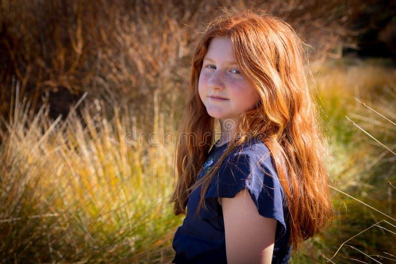 Chica joven con el pelo rojo largo contra un fondo natural otoñal fotografía de archivo libre de regalías