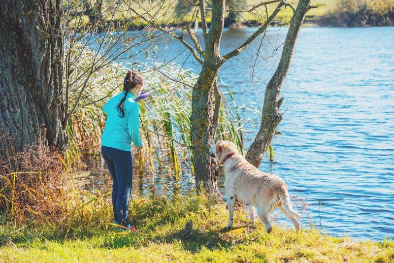 Chica joven con el perro en la orilla del lago imagen de archivo