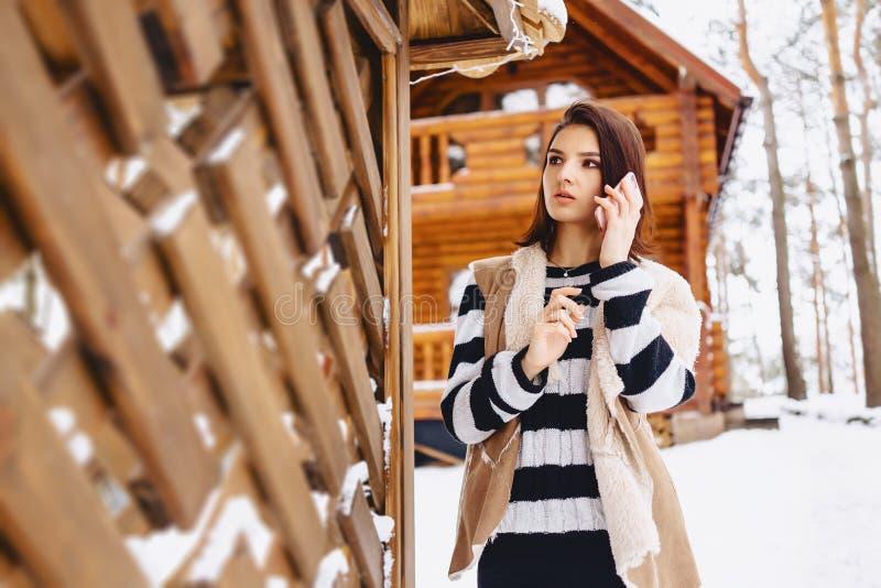 chica joven con el teléfono en chaleco encendido contra de la cabaña de madera foto de archivo