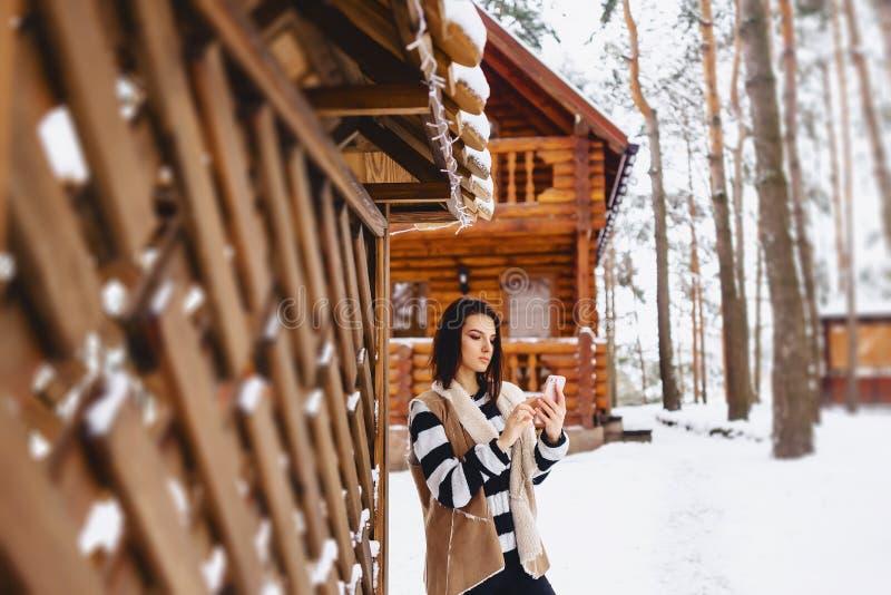chica joven con el teléfono en chaleco encendido contra de la cabaña de madera foto de archivo libre de regalías