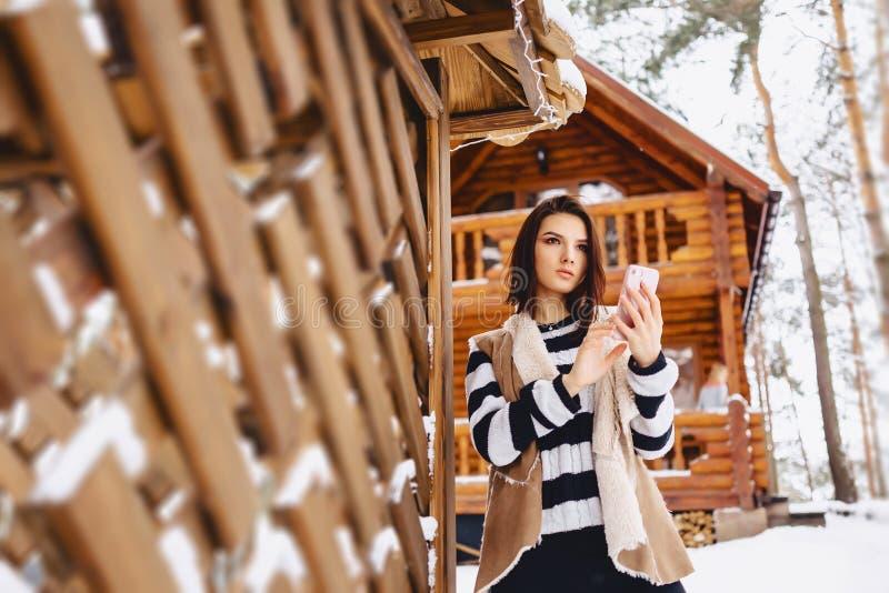 chica joven con el teléfono en chaleco encendido contra de la cabaña de madera fotos de archivo libres de regalías
