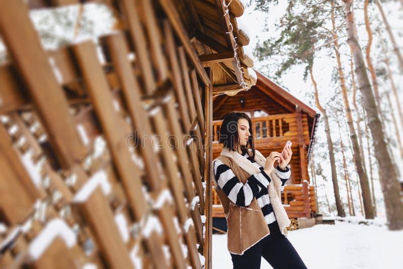 chica joven con el teléfono en chaleco encendido contra de la cabaña de madera imagen de archivo