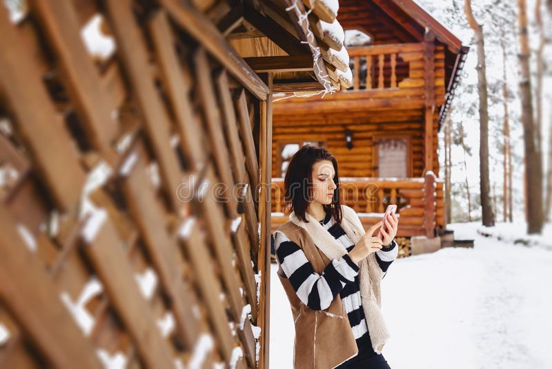 chica joven con el teléfono en chaleco encendido contra de la cabaña de madera fotografía de archivo