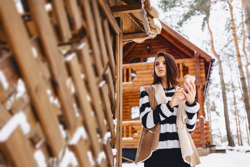 chica joven con el teléfono en chaleco encendido contra de la cabaña de madera fotografía de archivo libre de regalías