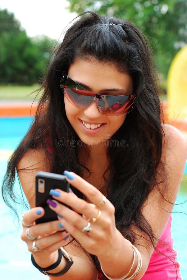 Chica joven con el teléfono móvil en parque del th imagen de archivo libre de regalías