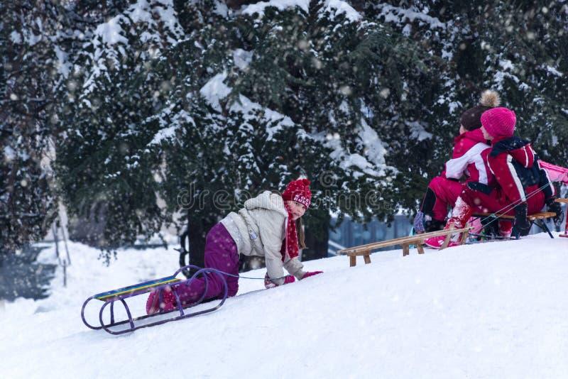Chica joven con el trineo que goza en nieve en parque de la ciudad de las colinas imagen de archivo libre de regalías