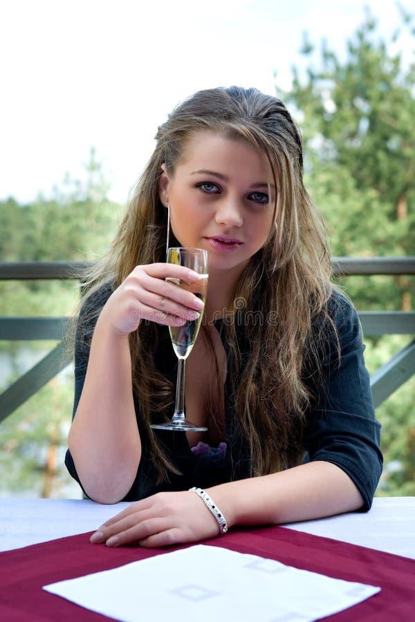 Chica joven con el vidrio de champán imagen de archivo