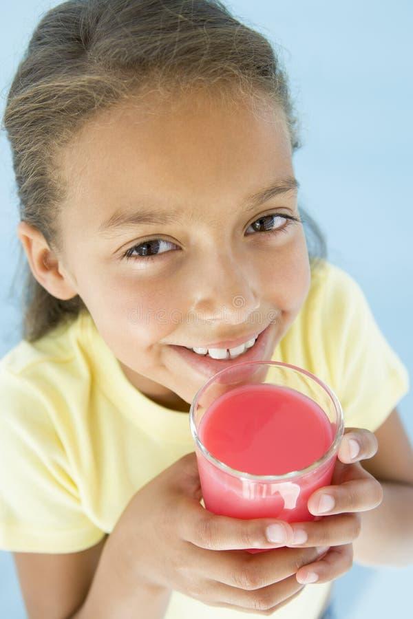 Chica joven con el vidrio de sonrisa del jugo fotos de archivo libres de regalías