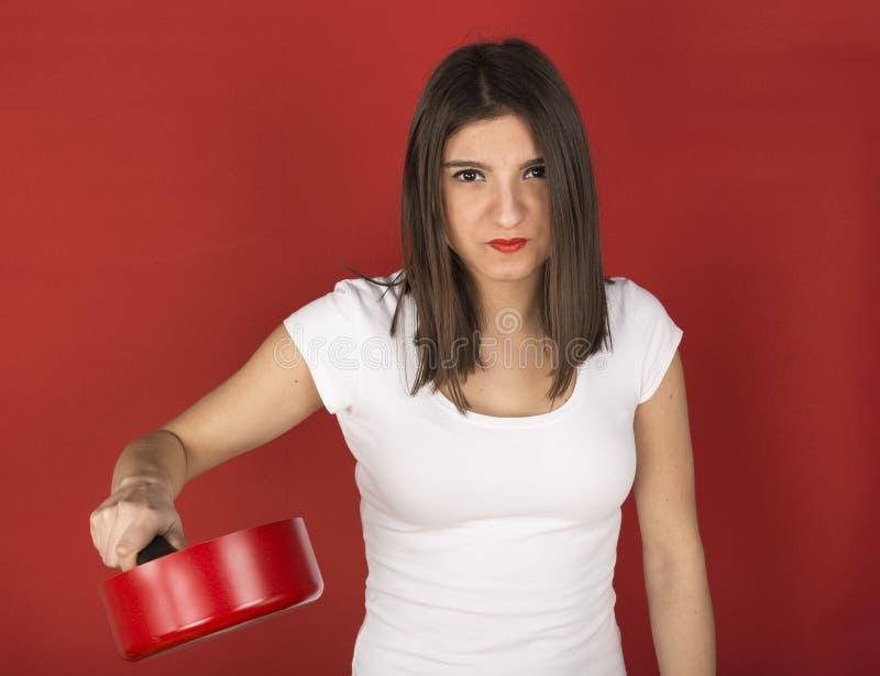 Chica joven con la cacerola roja fotografía de archivo