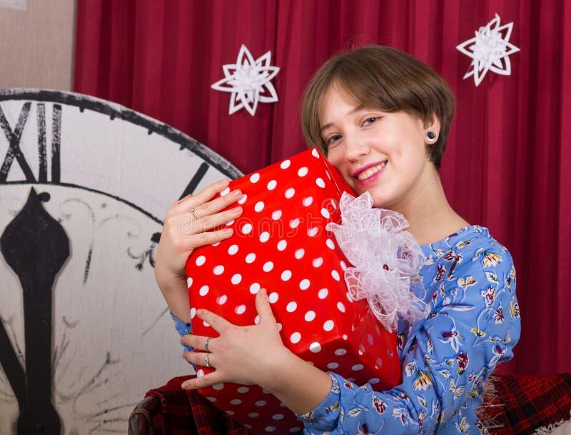 Chica joven con la caja de regalo en el fondo de las horas del Año Nuevo fotos de archivo
