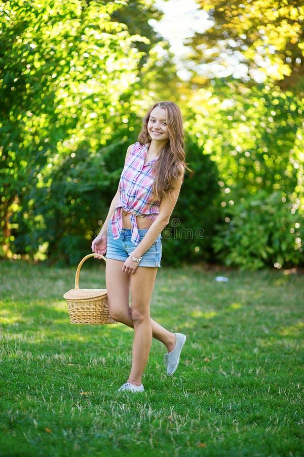Chica joven con la cesta que va a tener una comida campestre imágenes de archivo libres de regalías