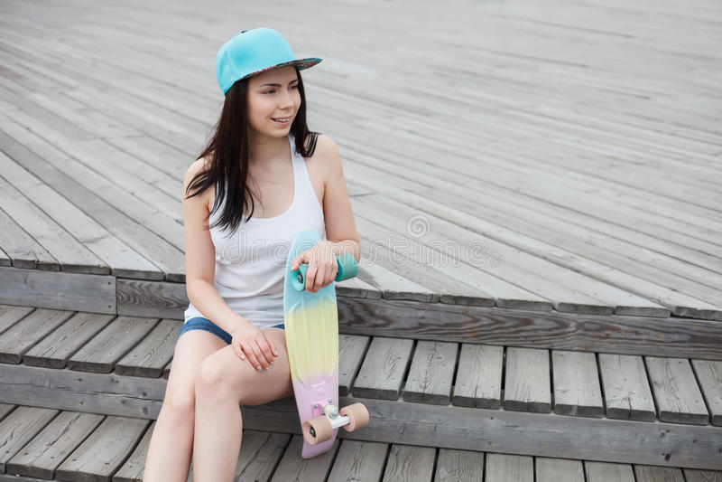 Chica joven con la cubierta corta del monopatín del crucero al aire libre foto de archivo